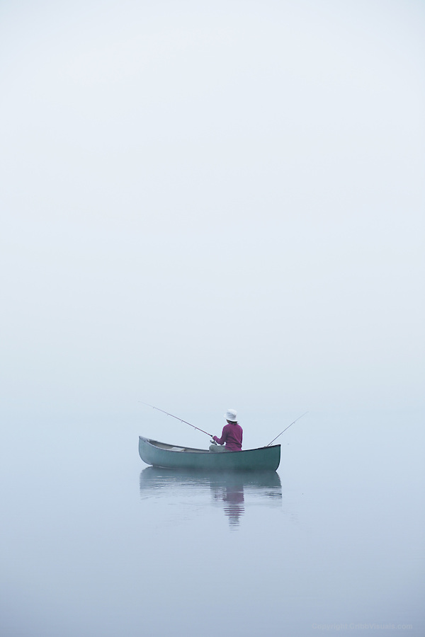 Hortonia, VT, USA - August 20, 2009: Girl fishing a lake from a canoe on a misty morning