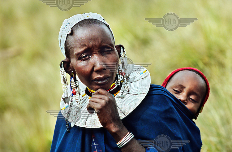 Maasai woman in traditional dress with baby in the Crater Highlands region, along the East African rift in Tanzania.