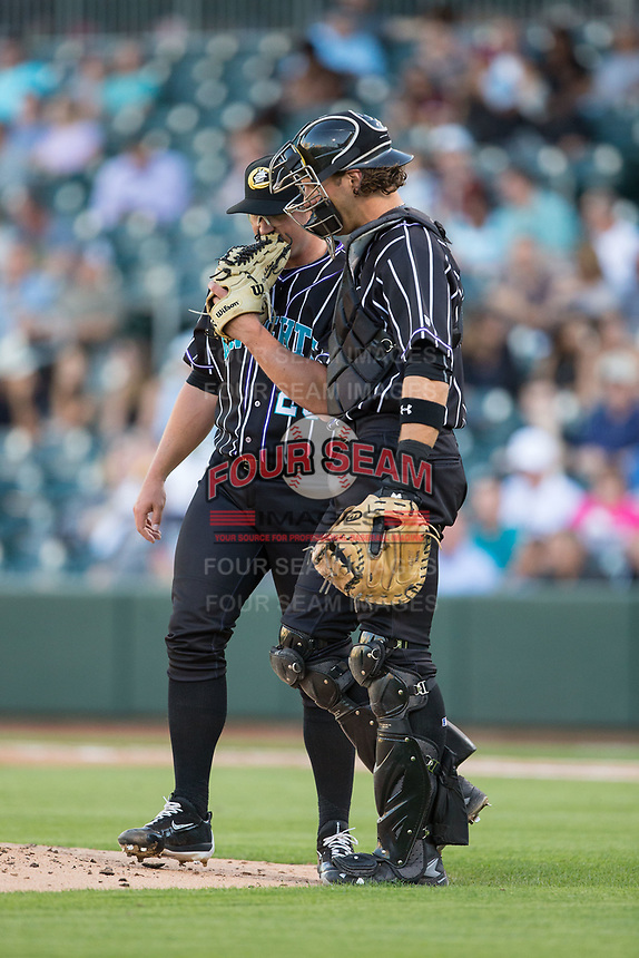 Charlotte Knights catcher Kevan Smith (32) has a meeting with starting pitcher Carson Fulmer (28) during the game against the Norfolk Tides at BB&T BallPark on May 2, 2017 in Charlotte, North Carolina.  The Knights defeated the Tides 8-3.  (Brian Westerholt/Four Seam Images)
