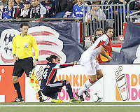 Last ditch defense by New England Revolution midfielder Lee Nguyen (24). D.C. United defender Dejan Jakovic (5) dribbles. In a Major League Soccer (MLS) match, the New England Revolution (blue) defeated D.C. United (white), 2-1, at Gillette Stadium on September 21, 2013.