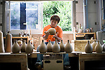 Daisuke Yonamine makes earthenware flasks for use in specially brewed awamori at the Chuko distillery in Naha, Okinawa Prefecture, Japan, on May 20, 2012. Photographer: Robert Gilhooly