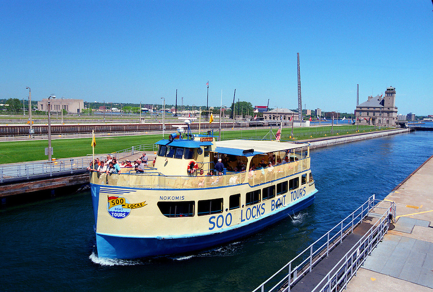 A TOUR BOAT MOVES OUT OF THE SOO LOCKS ON THE SAINT MARYS RIVER AND INTO LAKE SUPERIOR IN SAULT STE. MARIE MICHIGAN.