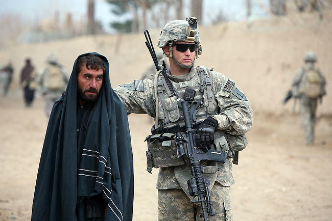 Sgt. Justin Chaney, 21, of Satellite Beach, Fla., a soldier with Company C, 2nd Battalion, 2nd Infantry Regiment, takes custody of a man suspected of being a Taliban fighter near the Maiwand bazaar in Kandahar province, Afghanistan. Jan. 3, 2009. DREW BROWN/STARS AND STRIPES
