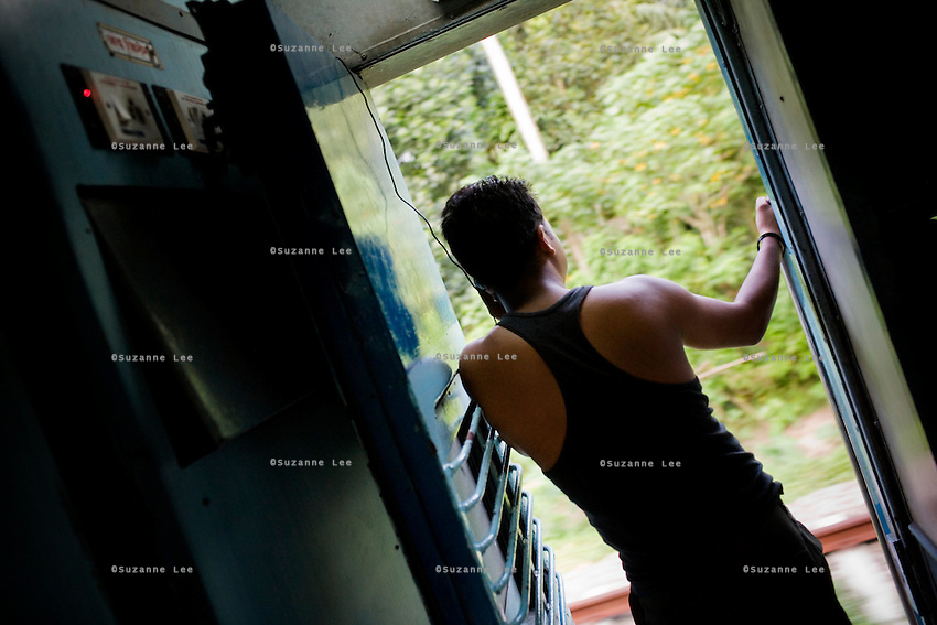 A passenger who hails from Dehra Dun, Uttaranchal, charges his mobile phone at the common plug point at the end of the sleeper coach, while he makes phone calls...Train passengers on the Himsagar Express 6318 going from Jammu Tawi station to Kanyakumari on 8th July 2009.. .6318 / Himsagar Express, India's longest single train journey, spanning 3720 kms, going from the mountains (Hima) to the seas (Sagar), from Jammu and Kashmir state of the Indian Himalayas to Kanyakumari, which is the southern most tip of India...Photo by Suzanne Lee / for The National