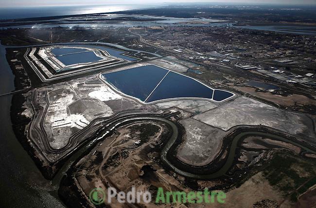 Imagen aérea de las balsas de fosfoyesos y la zona supuestamente regenerada (arriba izquierda). También puede observarse la ciudad de Huelva y apreciar la cercanía y dimensiones de las balsas. El residuo no se encuentra solo las piscinas, toda la zona gris son fosofoyesos secos. Se expulsa el residuo en estado líquido de la factoría y se almacena en esta zona. Seguidamente la evaporación lo transforma en solidó y el residuo se utiliza para levantar los diques de contención del nuevo residuo. En la zona trabajan operarios con maquinaria pesada sin protección de ningún tipo..Una inmensa mancha roja cubre la esquina suroeste de España. Los atlas.con los índices de mortalidad por cáncer del Instituto Carlos III muestran una.terrorífica tasa de muerte por diferentes tipos de tumores en la comarca de.Huelva. Los científicos sólo encuentran una explicación a esta acumulación.imparable y espeluznante de muertes..Una inmensa mancha cubre un extremo de la ciudad. Es más grande que la.misma ciudad, Huelva. Son los residuos de los fosfoyesos. Encorsetada.geográficamente por esta balsa y un tremendo polo petroquímico, la muerte.es una realidad que se calla. Es una vecina más, junto a decenas de.enfermedades endémicas por contaminación. (C) Pedro ARMESTRE