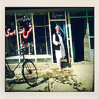 A man steps out of a shop into the Kabul sunshine.