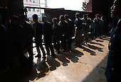"""Workers queue to exit the Grandsmart jeans factory in Zhongshan city, China. .This picture is part of a photo and text story on blue jeans production in China by Justin Jin. .China, the """"factory of the world"""", is now also the major producer for blue jeans. To meet production demand, thousands of workers sweat through the night scrubbing, spraying and tearing trousers to create their rugged look. .At dawn, workers bundle the garment off to another factory for packaging and shipping around the world..The workers are among the 200 million migrant labourers criss-crossing China.looking for a better life, at the same time building their country into a.mighty industrial power."""