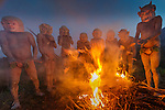 Asaro mudmen gather around a  fire, Eastern Highlands Province, Papua New Guinea