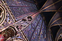 View from below of a statue of apostle against the stained glass clerestories of the nave of the upper chapel of La Sainte-Chapelle (The Holy Chapel), 1248, Paris, France. La Sainte-Chapelle was commissioned by King Louis IX to house his collection of Passion Relics, including the Crown of Thorns. Fifteen huge mid-13th century windows fill the nave and apse of La Sainte-Chapelle, considered among the highest achievements of the Rayonnant period of Gothic architecture. Picture by Manuel Cohen