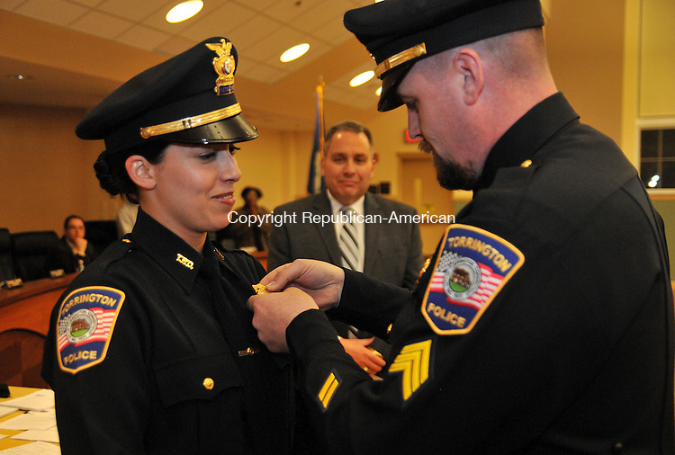 TORRINGTON, CT, 04 MARCH 15 - Detective Nicole Santiago is pinned with her new rank Wednesday by her husband Sgt. Greg Witiak as Police Chief Michael Maniago looks on at City Hall.   Alec Johnson/ Republican-American