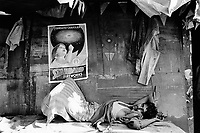 """India. Province of Gujarat. Alang. A worker, a sick man suffering from malaria, lays on his back and rests on a bench on the doorstep of his wood house. A poster for the """" Standard Fireworks"""" brand shows a girl using a firework. The advertisement is taped on the wall. Alang, located in the Gulf of Khambhat, is a ships breaking place and is considered as the biggest scrapyard in the world. © 1992 Didier Ruef"""