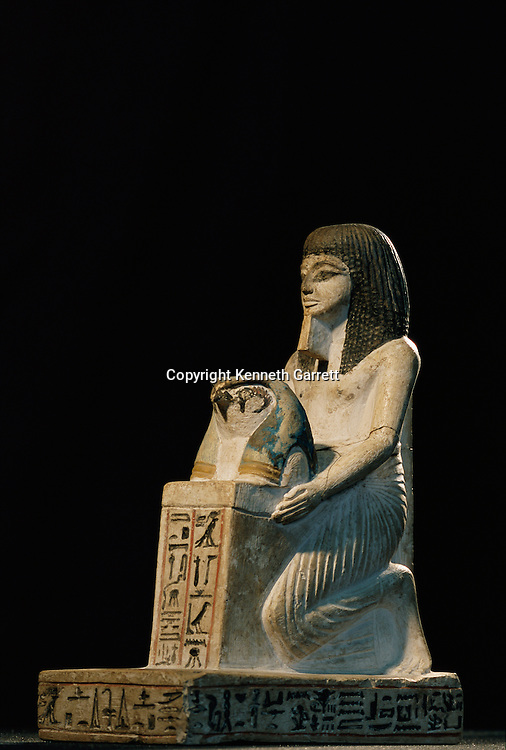 Painted limestone statue of Amenemope offering a naos with the head of a falcon on top, New Kingdom