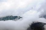A small plane glides through heavy clouds near the mountain tops in Juneau, Alaska