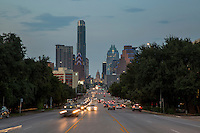 Cars drive past the Congress Avenue Bridge the gateway to the hip and eclectic South Congress Avenue and South Austin with the Texas State Capitol and downtown skyline backdrop - Stock Image.
