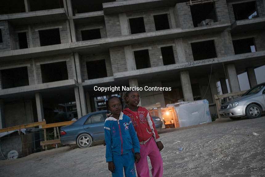 November 11, 2014 - Tripoli City, Libya: Tawerghan young girls are seen walking in a construction site in the Fallah road of Tripoli used as a temporary shelter after the Tawerghans were forced to move from their city home as they were harassed by the armed militias of Misrata during the 2011 uprising against Colonel Gaddafi. (Photo/Narciso Contreras)