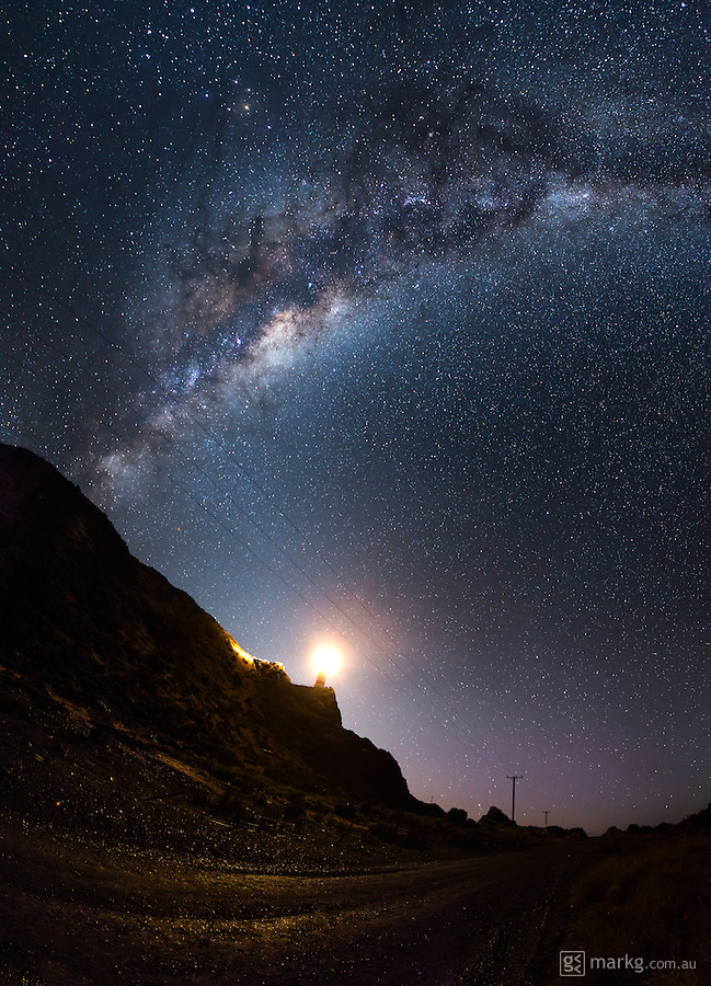 The Milky Way towers above a remote road on the southern most point of the North Island of New Zealand. The light on the hill is the Cape Palliser Lighthouse, which was built in 1897 and includes a climb of 250 steps from the road to the lighthouse on the hill top. This image is a stitch of 8 individual images all shot at 24mm and stitched together in Autopan.