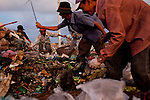 Families dig through trash trying to salvage anything they can recycle or sell at the garbage dump outside of Rach Gia, Vietnam.  These families live in make-shift houses inside the garbage dump.