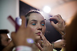 A model for the Brazilian brand, Triton, gets her hair and make-up worked on backstage at São Paulo Fashion Week for Summer Season 2013/2014, at Bienal, in São Paulo, Brazil, on Wednesday, March 20, 2013.