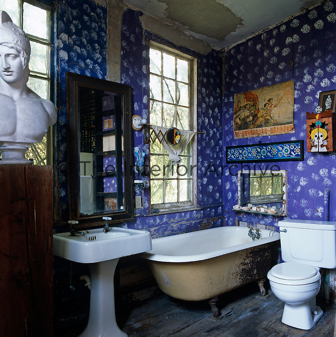 The dilapidated bathroom has purple walls decorated with white sponge-work polka-dots and a bust of Mars