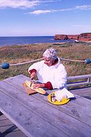 Ile de Cap-aux-Meules, Iles de la Madeleine, Quebec, Canada - Model Released Woman cutting Baguette on Picnic Table, at La Belle Anse along Gulf of St. Lawrence - (Beautiful Cove, Grindstone Island, Magdalen Island