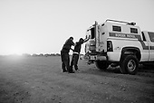 Calexico, California<br /> USA<br /> August 20, 2007<br /> <br /> Border patrolmen run after a Mexican man that illegally jumped the border fence near the official border crossing. <br /> <br /> He is captured but two others escape into the US.