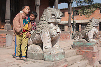 Kathmandu, Nepal.  Two Nepali Boys and Snow Leopard Guarding Neglected Hindu Temple.