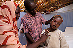 In the Ardabba IDP Camp near Garsila, in Sudan's war-torn Darfur region, ACT-Caritas provides primary health care -- including the services of Dr. Robert Lobor (center)-- to displaced families as well as members of the local host community.