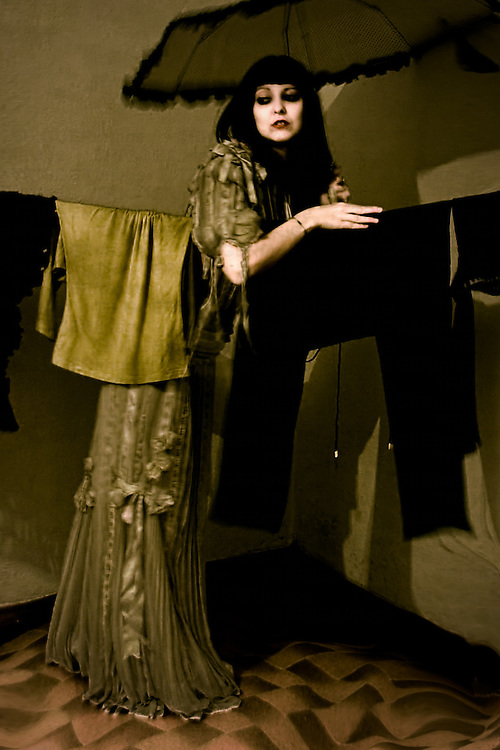 A young woman wearing a long dress holding an umbrella indoors leaning over a clothes line