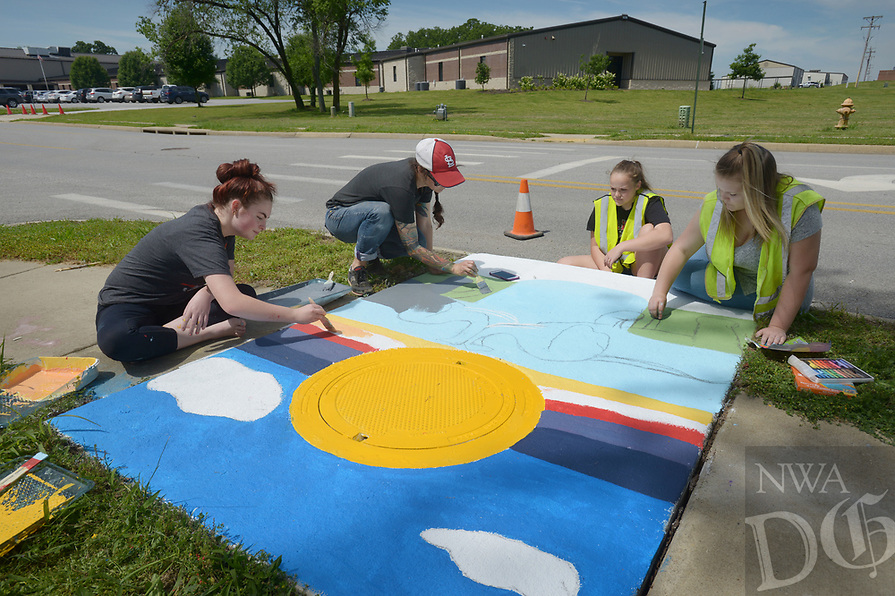 NWA Democrat-Gazette/BEN GOFF @NWABENGOFF<br /> Anya Bruhin (second from left), Pea Ridge Middle School art teacher, helps students from her 8th grade elective art class Kyleigh Box (from left), Sadie Prince and Kailey King paint their design Monday, May 15, 2017, as Pea Ridge Mayor Jackie Crabtree stops by to take a look, along Weston Street in front of the school in Pea Ridge. Students in the class partnered with UpStream Art to learn about water quality issues before working in small groups to designs and paint murals on six storm drains near the school.