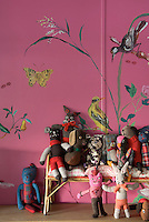 A collection of handmade soft toys sitting on a tiny sofa against a pink wall featuring a hand-painted bird mural
