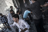 A Syrian civilian screams horrified as a group of men find the body of a dead man among the debris of a demolished house building while they were lookng for the victims of an aircraft shelling just some minutes after the house was targeted by one army plane at Tarik Albab neighborhood in the northeastern of Aleppo City. The Syrian army is carrying out aircraft shellings over residential areas throughout Aleppo City, killing hundreds of civilians in its attempt to sweep out the rebels.