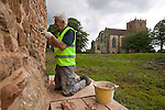 A man works to restore Astley Castle for the Landmark Trust in Warwickshire, the United Kingdom. In the background a ancient stone church. Astley Castle is a building belonging to the Landmark Trust, a United Kingdom building preservation charity that rescues historic buildings at risk and gives them a new life as places to stay in and experience.