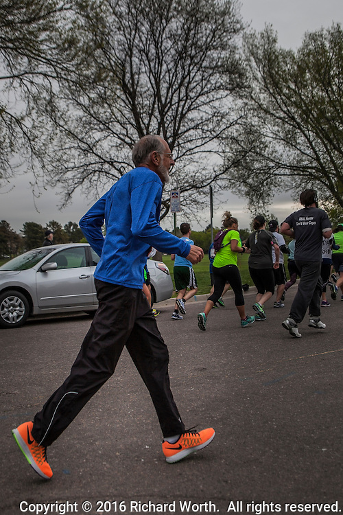 Long stride in orange shoes - an over 70 runner along the half marathon course at the 2016 Colfax Marathon, Denver, Colorado.