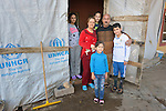 Saeed Elyas Seno and his wife Ekhlas Jomaa pose along with their four children in the door of their temporary home in Dohuk, Iraq. The Yazidi family was displaced from Bashiqa, Iraq, by the Islamic State group in 2014. Seno participates in a skills training program sponsored by the Christian Aid Program Nohadra - Iraq (CAPNI).