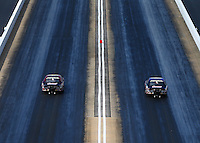 Jun 17, 2016; Bristol, TN, USA; NHRA pro stock driver Greg Anderson (left) races alongside teammate Jason Line during qualifying for the Thunder Valley Nationals at Bristol Dragway. Mandatory Credit: Mark J. Rebilas-USA TODAY Sports