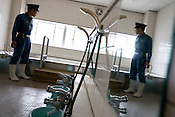 A prison warder inspects the communal bath and shower area for elderly prisoners, in Onomichi prison , Japan. May 19th 2008