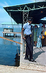Police guard with gun eyeing the photographer. At embarkation port. Images of the capital,Port au Prince, Haiti 1975