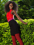 Smiling young stylish black woman in colorful clothes in a park