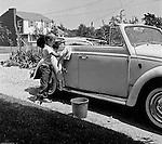 Bethel Park PA:  View of Michael Stewart washing the Stewart's new Volkswagen Beetle convertible - 1959.