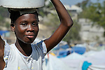 A girl carries water in a camp for homeless families set up on a golf course in Port-au-Prince, Haiti, which was ravaged by a January 12 earthquake.