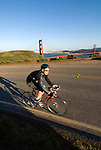 California: Bicyclist at Golden Gate Bridge, view of Golden Gate Bridge and city.  Photo # 3-casanf78403. Photo copyright Lee Foster.