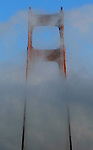 A vertical image of the San Francisco north tower of Golden Gate Bridge surround in fog.