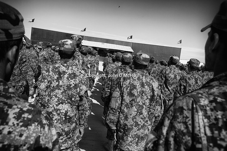Afghan National Army soldiers take part in a swearing in ceremony at the Regional Training Centre in Helmand, 08 Nov 2012. Placing their hands on a Koran, they take an oath to defend Afghanistan. (John D McHugh)