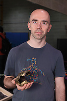 Origami designer and folder Goran Konjevod, California, USA, holding one of his designs cast in bronze
