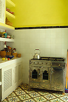 The simple kitchen has a chrome range and a beautiful patterned tile floor