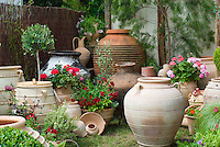 Variety of terracotta pottery pots, urns containers, annual geraniums, herbs, container garden and ornaments