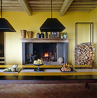 The ancient fireplace in this kitchen is seen across the contemporary yellow and black stripes of the vast kitchen table