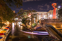 This is one of my favorite images because it captured the cityscape at night of the river walk with the colorful umbrellas at Cafe Ole restaurant with the light trail created from the tour boats as they go under the pedestrian bridge with the city's Torch of Friendship on the street above. Watermark will not appear on image