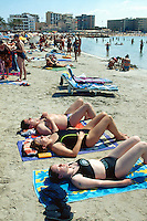"Spain. Mallorca in the Balearic islands. Palma. Tourists take a rest, sunbathe and sleep on plastic chairs in the sandy beach of "" Playa de Palma"". Mediterranean sea. © 1999 Didier Ruef"