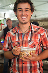 The extremely popular Saturday Portland Farmers' Market, located in the South Park Blocks near the Portland State University Campus, offers a large selection of locally grown organic produce, fish, meat and foodstuffs.  Pictured here is Freddy Guy Hazelnuts where Cooper Paradise hands out samples of the roasted filberts.